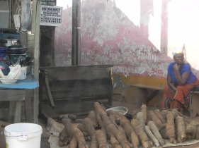Market Merchant selling her yams. These are used to make fufu and other Ghanaian dishes.