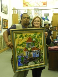 Teresa Green is pictured with 1 of her paintings, Blue House Brown Door - A Sunday Conversation